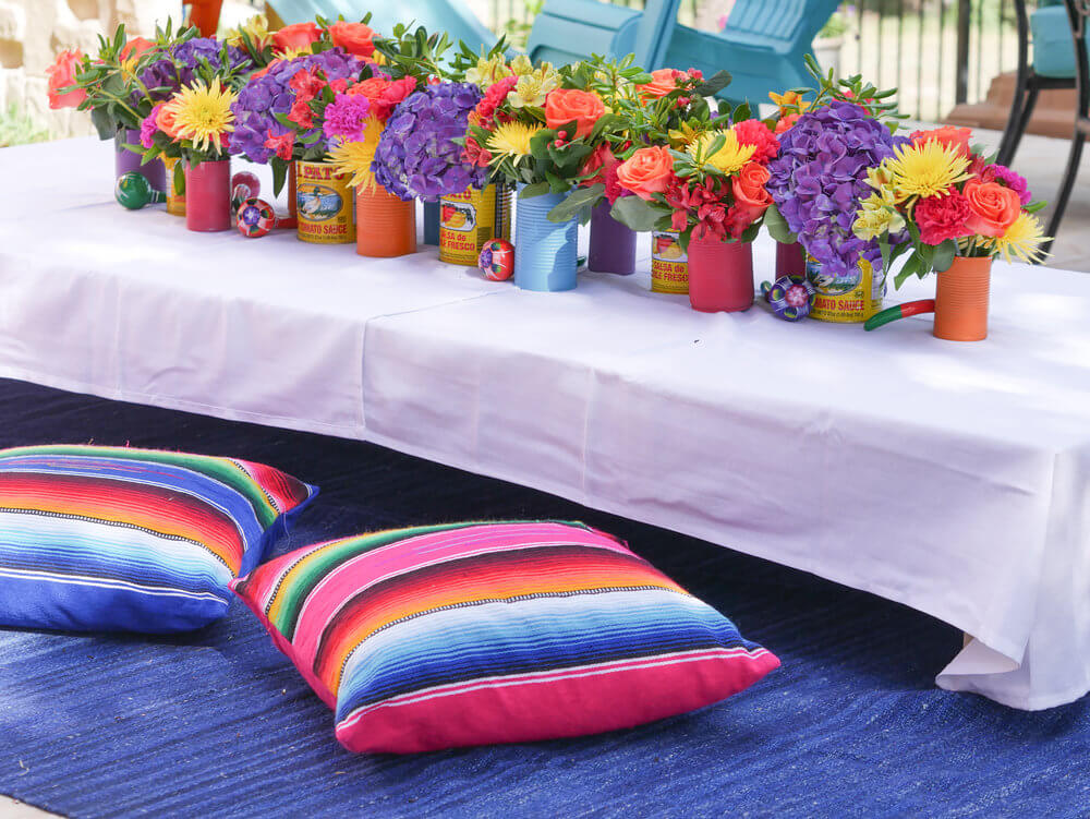 Kids table, complete with colorful Mexican themed pillows to sit on, and recycled cans filled with colorful flowers.