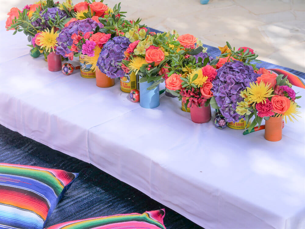 This kids table with a beautiful centerpiece of recycled cans and fresh flowers is just perfect for a fiesta themed birthday party. Styling by Austin Texas party planner Mint Event Design www.minteventdesign.com #kidsbirthdayparty #fiestaparty #disneycoco #partyideas #girlbirthdayparty #cocobirthdayparty #floralcenterpiece