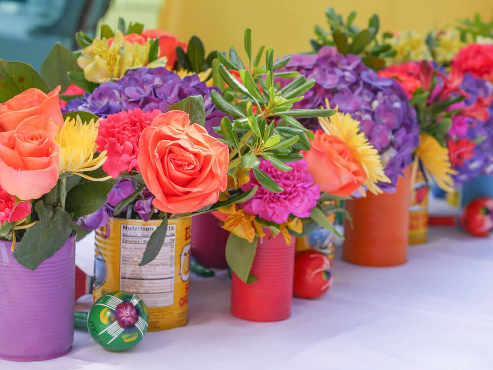 Creative Party Idea for a Floral Centerpiece . . . Use tin cans - painted and recycled food cans and fill with colorful fresh flowers. Maracas tucked in are just perfect for the kids party table at this Coco inspired fiesta birthday party. Styling by Austin Texas party planner Mint Event Design www.minteventdesign.com #kidsbirthdayparty #fiestaparty #disneycoco #partyideas #girlbirthdayparty #cocobirthdayparty #floralcenterpiece