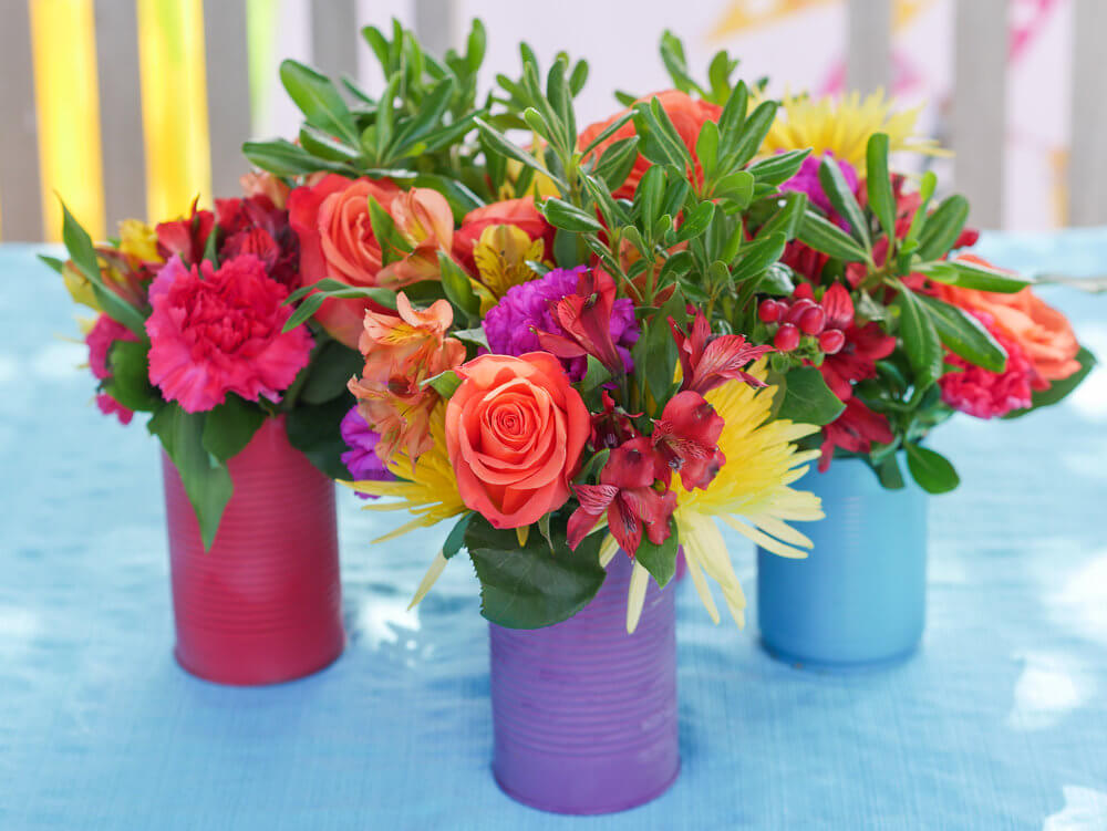 Fresh flowers in painted tin cans are the perfect centerpiece idea for a fiesta parties. Styling by Austin Texas party planner Mint Event Design www.minteventdesign.com #fiestaparty #partyideas #floralcenterpiece