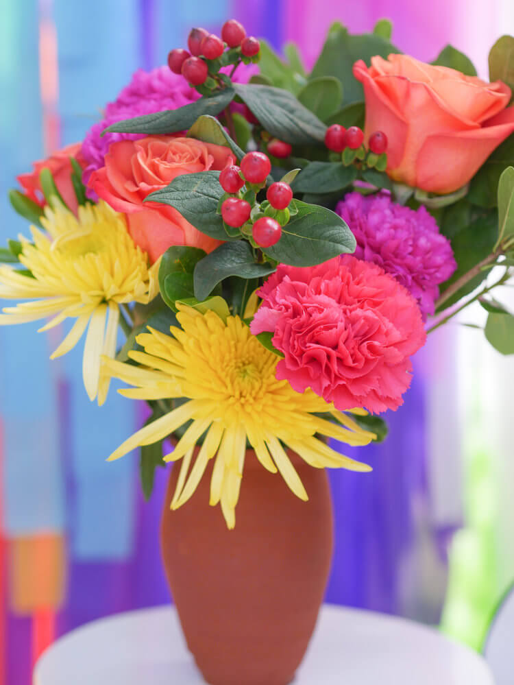 Fiesta flowers in a clay pot are such an easy centerpiece with a big statement at this fiesta.