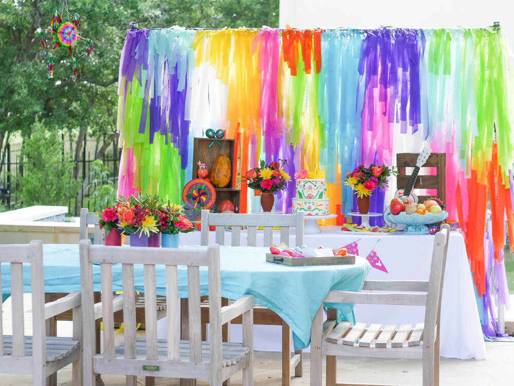 Fun, colorful, and festive fiesta party outside. From the dessert table to the guest table, not a detail was missed. This colorful background made such an impact. See more at www.minteventdesign.com #kidsbirthdayparty #fiestaparty #disneycoco #partyideas #girlbirthdayparty #cocobirthdayparty