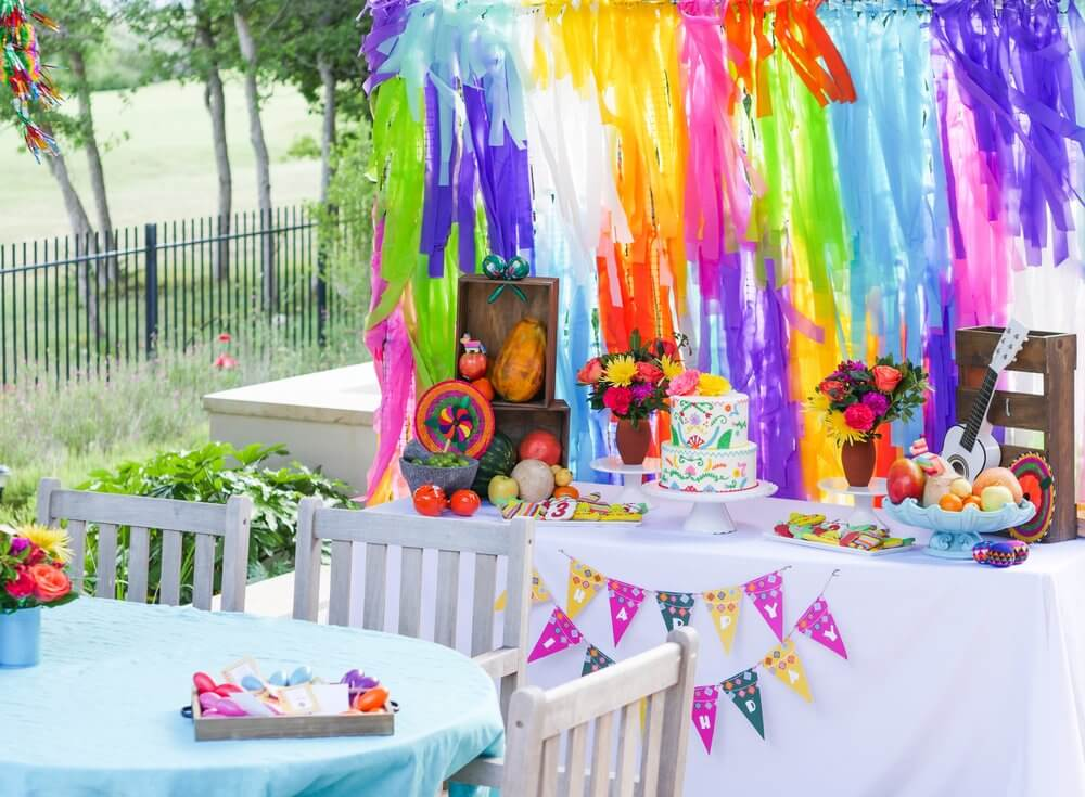 A fun and colorful outdoor Coco themed fiesta for a fun 3 year old, complete with dessert table and streamers backdrop.
