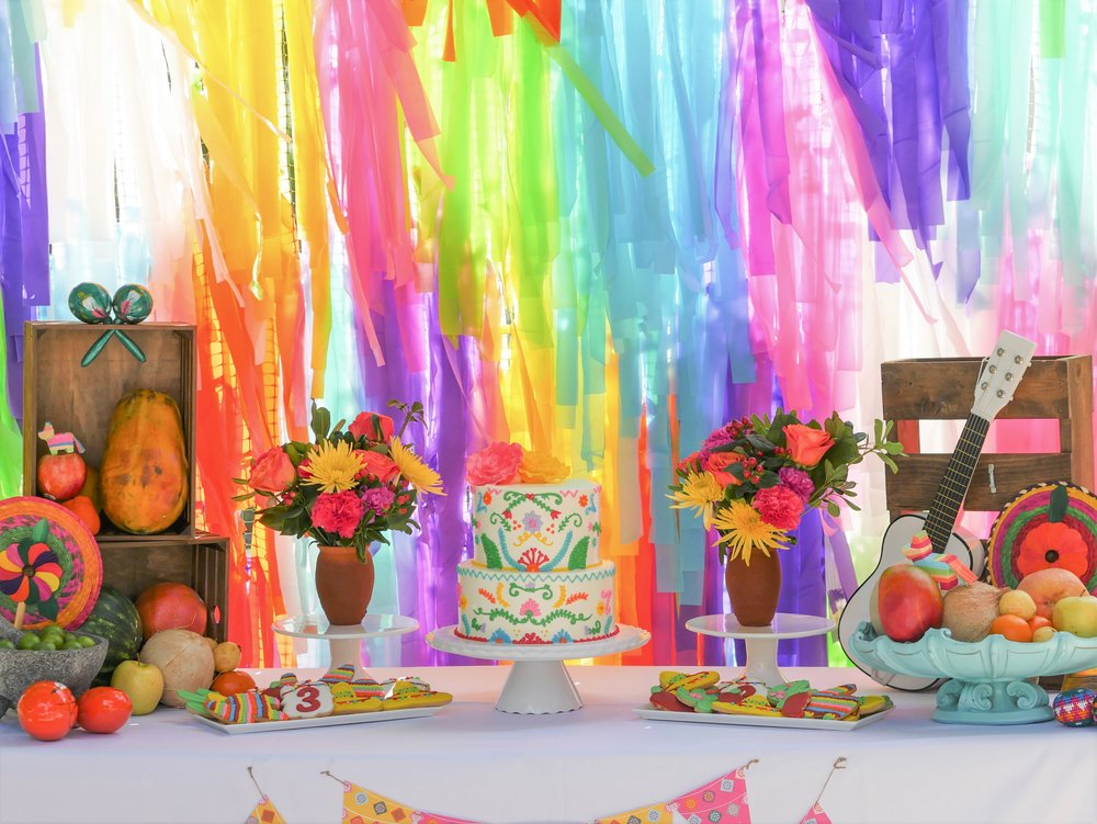 Birthday party fiesta table design and dessert table. Complete with Disney Pixar Coco themed cake, cookies, and mini guitars. Love how this colorful backdrop came out.