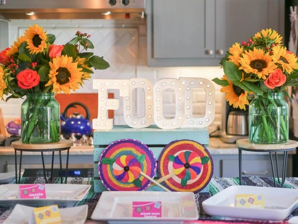 Food table was decorated with traditional Mexican decor, fiesta themed food cards, and flowers. FOOD marquee sign was the perfect touch.