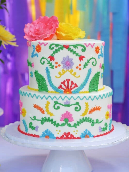 Beautiful fun Mexican decorated two-tier cake for a fiesta birthday party. Party Planning by Austin Texas party planner Mint Event Design www.minteventdesign.com #kidsbirthdayparty #fiestaparty #disneycoco #partyideas #girlbirthdayparty #cocobirthdayparty #birthdaycake