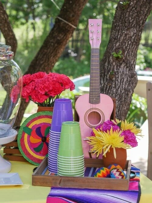 Tray filled with colorful drink cups, pink mini guitar, flowers, and Mexican decor to set the state for a Coco themed party.