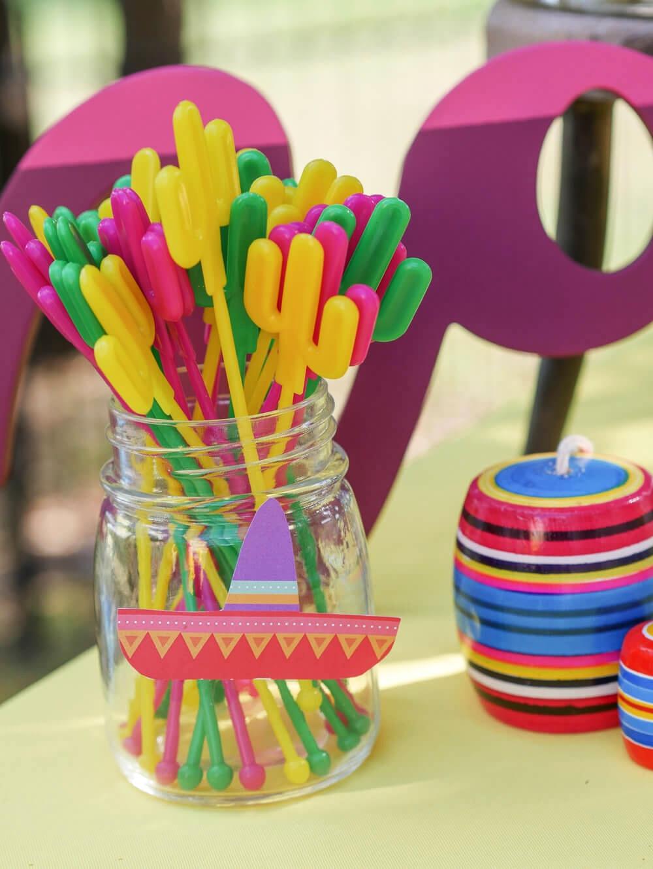 Cactus beverage stir sticks, paper sombrero, and traditional Mexican decor.