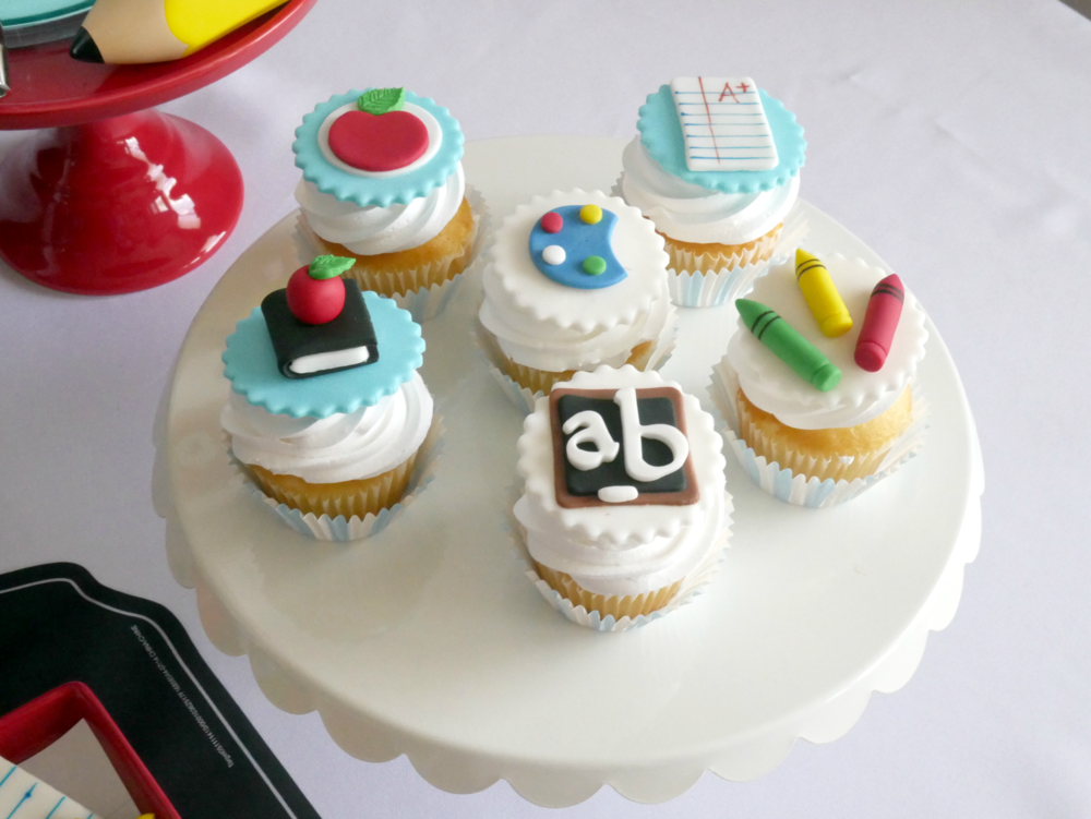 Vanilla cupcakes with back to school themed toppers made out of fondant