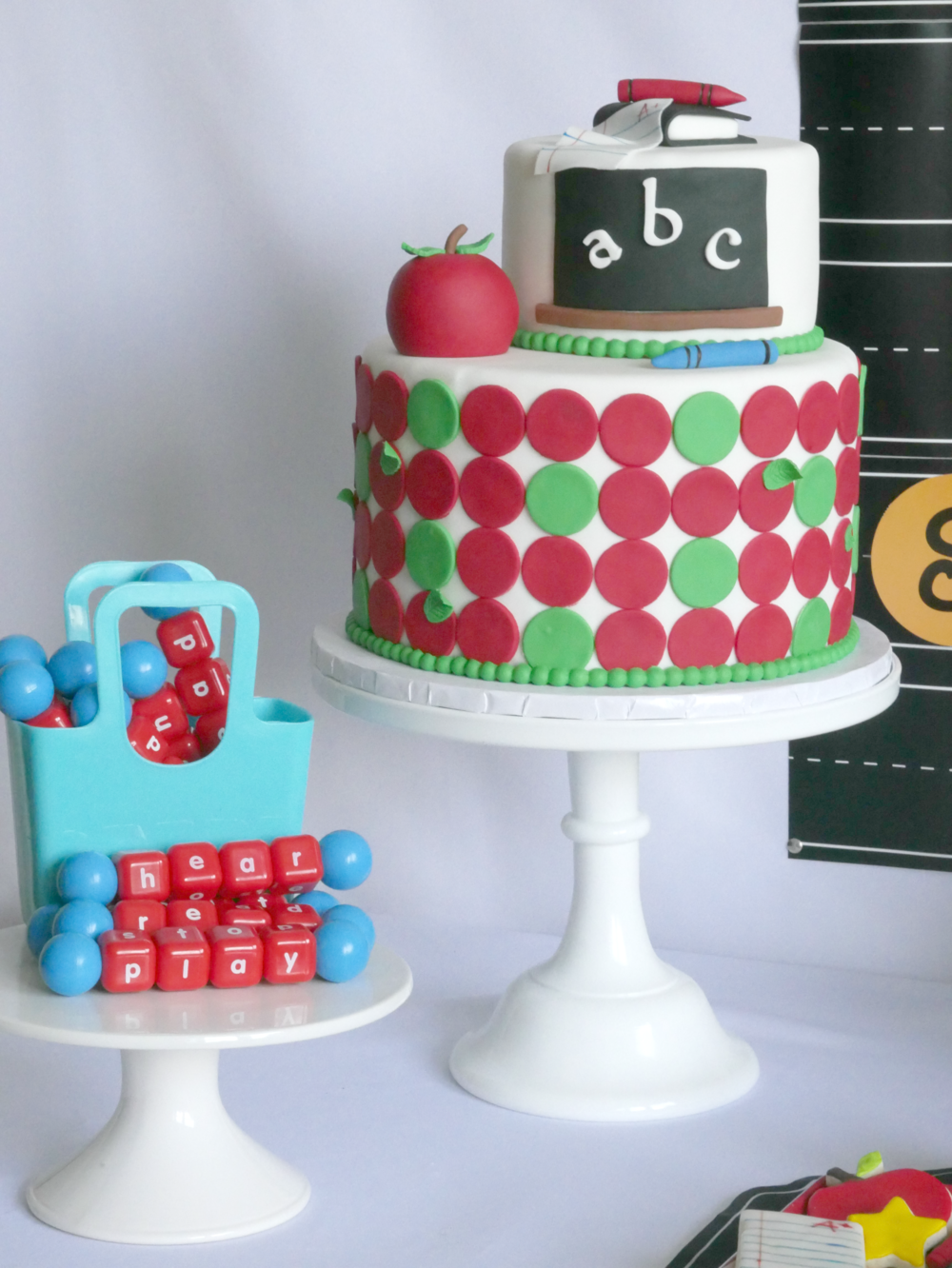 Two tiered school themed cake, with spelling toys perfect for a back to school party! Love all the party decorations and desserts.