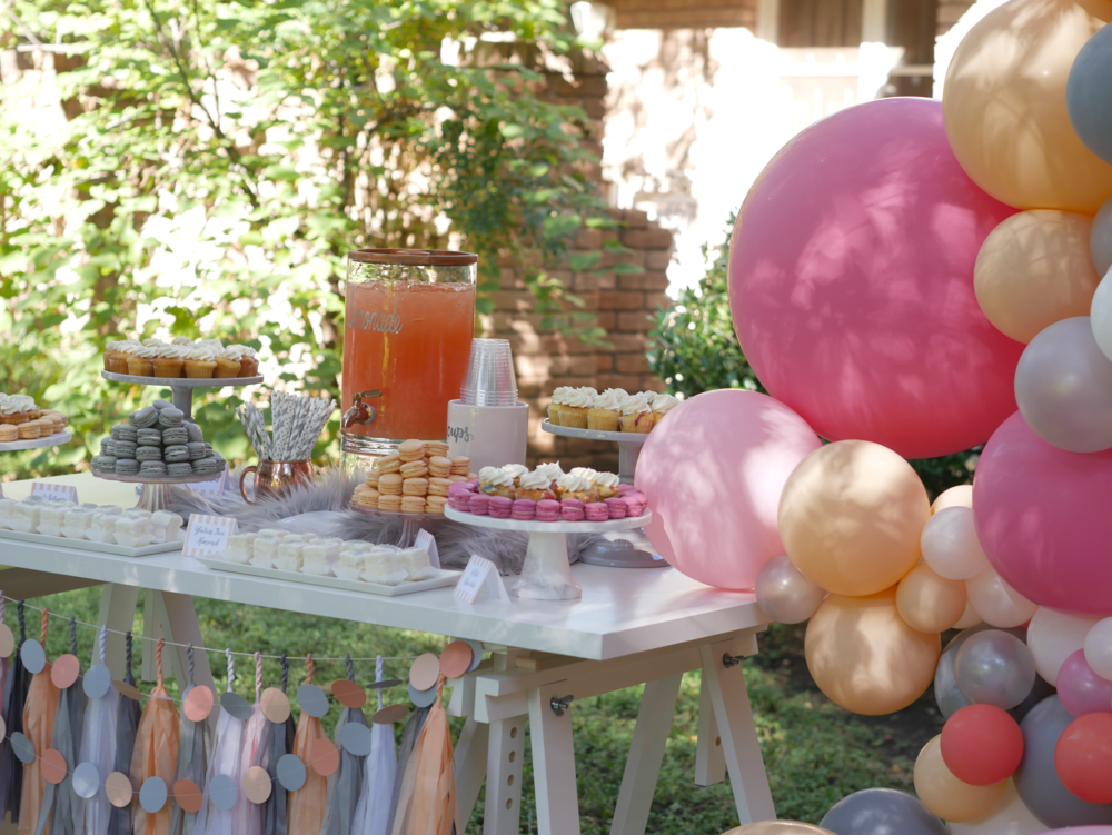 Gray and peach touches on a dessert table, includes a gorgeous balloon garland and a variety of desserts. Styled by Carolina from MINT Event Design i Austin Texas