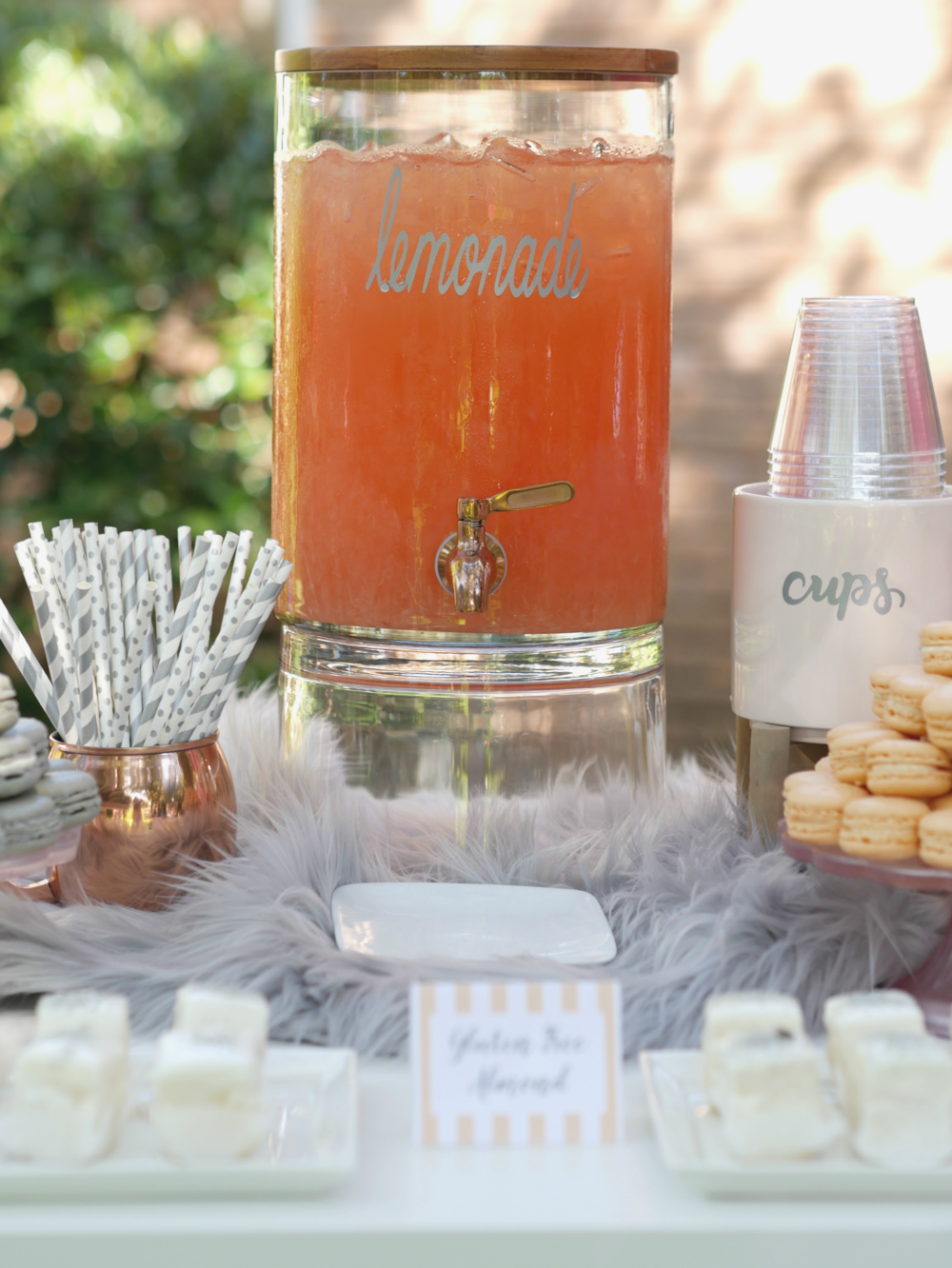 A chic lemonade stand idea, served with a variety of desserts.