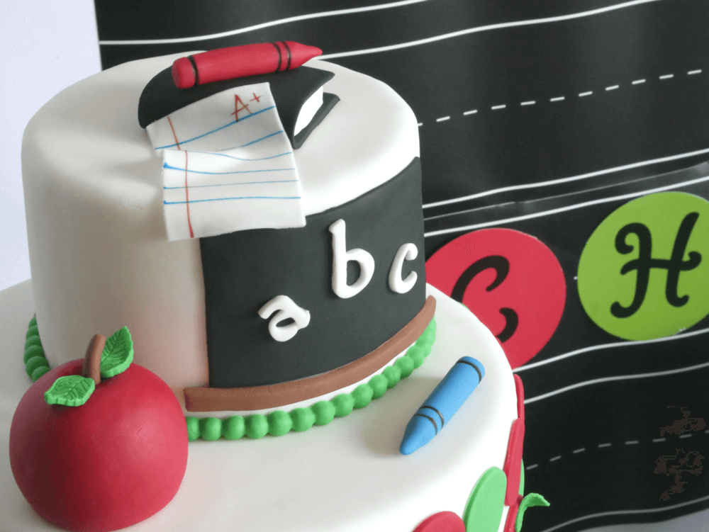 Adorable and detailed two tiered cake for a back to school party, with apples, crayons and a fondant chalkboard & letters.