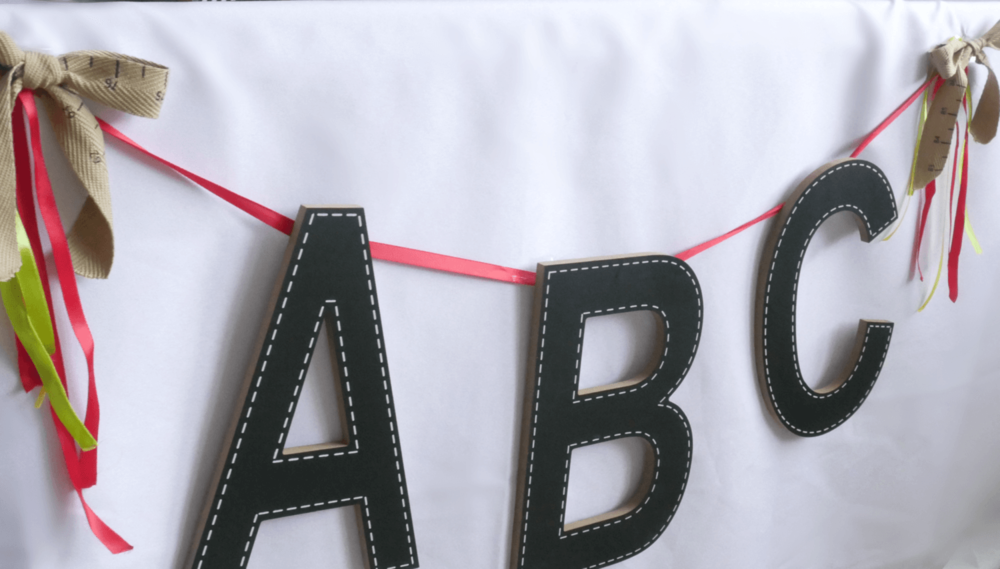 Cute and Rustic ABC banner at a colorful back to school party. Love the detail of the measuring tape ribbon.
