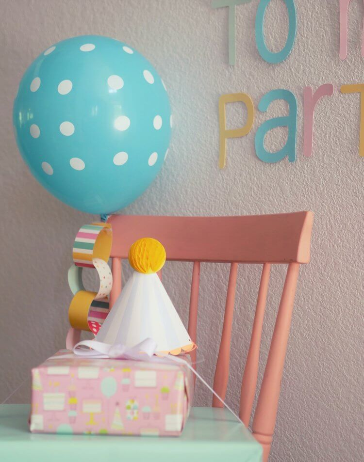 A sweet handpainted chair to hold birthday presents greets guests as they enter the party / Come see the Birthday Party Styled by Carolina from MINT Event Design / www.minteventdesign.com #birthdayparty #partyideas #partyinspiration #birthdayballoon