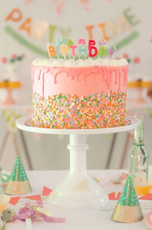 A birthday party cake that was inspired by the birthday party invitation - complete with sprinkles and Happy Birthday letter candles / Click to see even more surprising ways to greet your guests at a Birthday Party / Styled by Carolina from MINT Event Design / www.minteventdesign.com #birthdayparty #partyideas #partyinspiration #partydesserts #birthdaycake