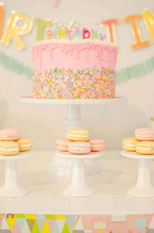 A birthday party cake that the birthday party invitation featuring sprinkles and drip frosting. Also offered guests color matching macarons / Click to see even more surprising ways to greet your guests at a Birthday Party / Styled by Carolina from MINT Event Design / www.minteventdesign.com #birthdayparty #partyideas #partyinspiration #partydesserts #birthdaycake #macarons