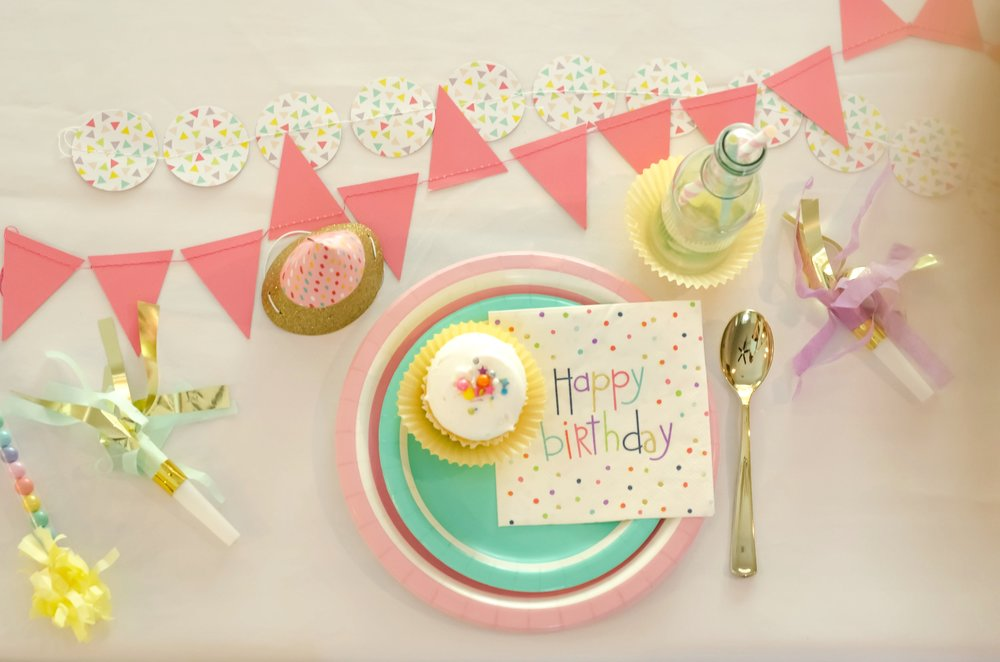 Create a fun party table centerpiece with paper banners and bunting as the table runner / Be sure to click for more surprising ways to greet your guests at a Birthday Party / Styled by Carolina from MINT Event Design / www.minteventdesign.com #birthdayparty #partyideas #partyinspiration #partytable #tabledecor #tabledecorations