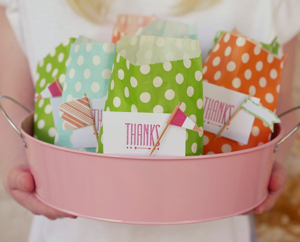 Present your party favors with fun polka dot paper bags with cute flags attached to the thank you tag / Be sure to click for more surprising ways to greet your guests at a Birthday Party / Styled by Carolina from MINT Event Design / www.minteventdesign.com #birthdayparty #partyideas #partyinspiration #partyfavors #favorbags #thankyougifts