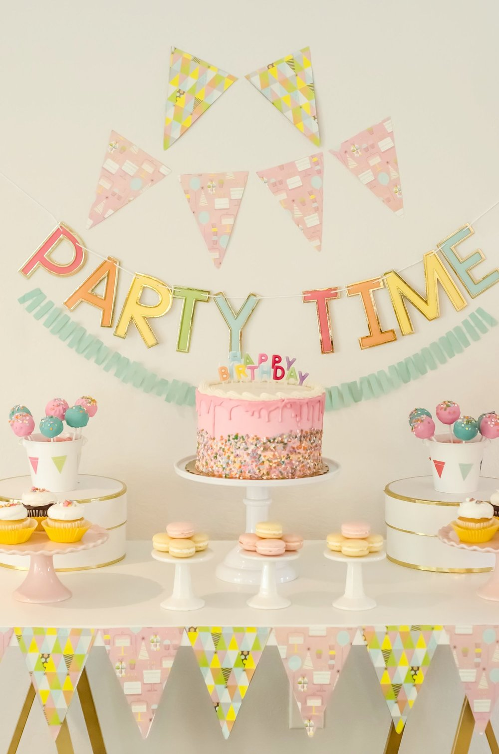 It's Party Time with this girl birthday party dessert table set up - featuring patterned bunting and color matching desserts with a Party Time Banner / Click to see even more surprising ways to greet your guests at a Birthday Party / Styled by Carolina from MINT Event Design / www.minteventdesign.com #birthdayparty #partyideas #partyinspiration #partydesserts #cakepops #partydessert #desserttable #partybanners #birthdaycake