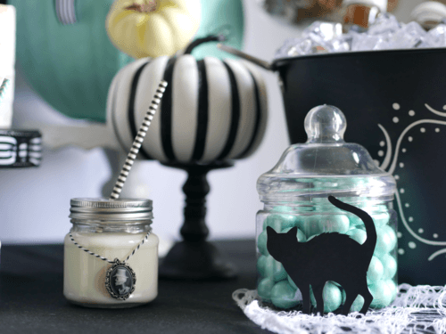 Skeleton Cameos, black cat silhouettes on apothecary jars and pops of teal created a modern Halloween party style. Come see the entire Halloween party by stylist Mint Event Design. #halloweenparty #partyideas #partyinspiration #halloween #halloweenideas #halloweendecor #halloweendecorations #halloweenpumpkins