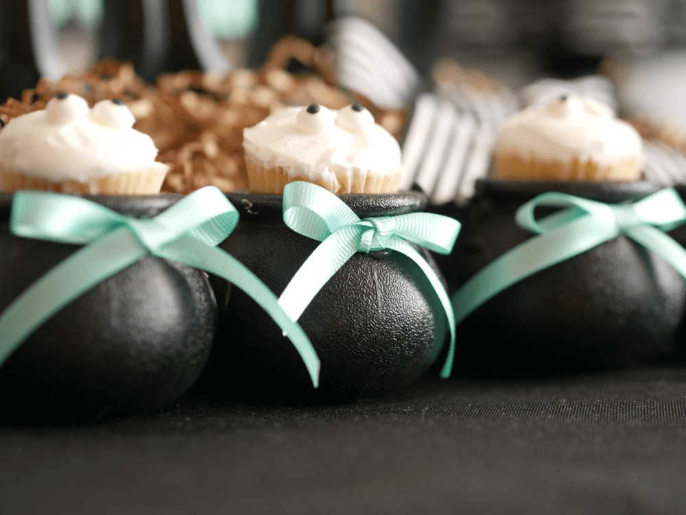 Love these mini cauldrons with mini cupcakes. Such a fun way to present a dessert. To up the spook factor, they have little candy eye balls on them. Come see even more Halloween party ideas from stylist Mint Event Design. #halloweenparty #partyideas #partyinspiration #halloween #halloweenideas #halloweendecorations #halloweencupcakes #halloweendesserts
