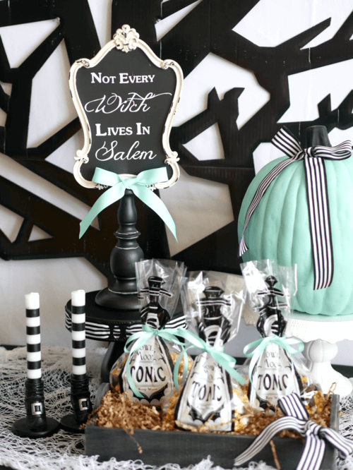 Super cute treat bags and adorable witch's boot candles at a modern teen Halloween Party. Super fun sign and tonic party favor bags. Click to see all the fun party details from this Modern Halloween Party on the Mint Event Design blog. #halloweenparty #partyideas #partyinspiration #halloween #halloweenideas #halloweendecorations #halloweensdecor #partyfavors #halloweenfavors