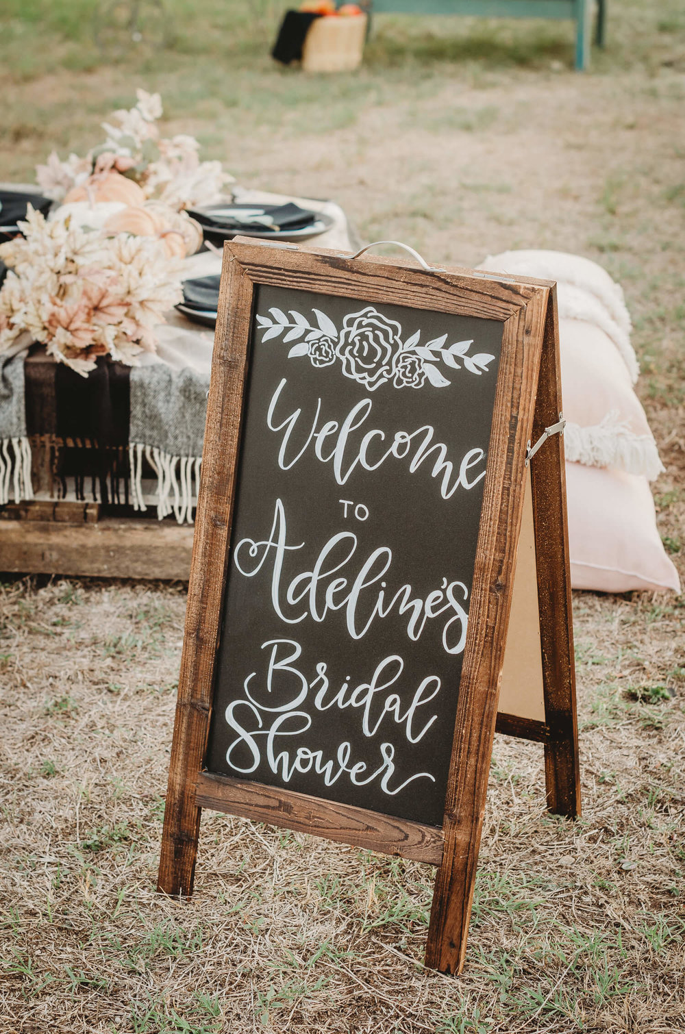 Greet wedding guests with a rustic wooden chalkboard sign welcoming them to your event. Click to see all the details of this fall bridal shower by party stylist Mint Event Design. #bridalshowers #bridalshowerideas #rusticwedding #rusticbridalshower #bridalshowerdecor #farmwedding #chalkboardsign