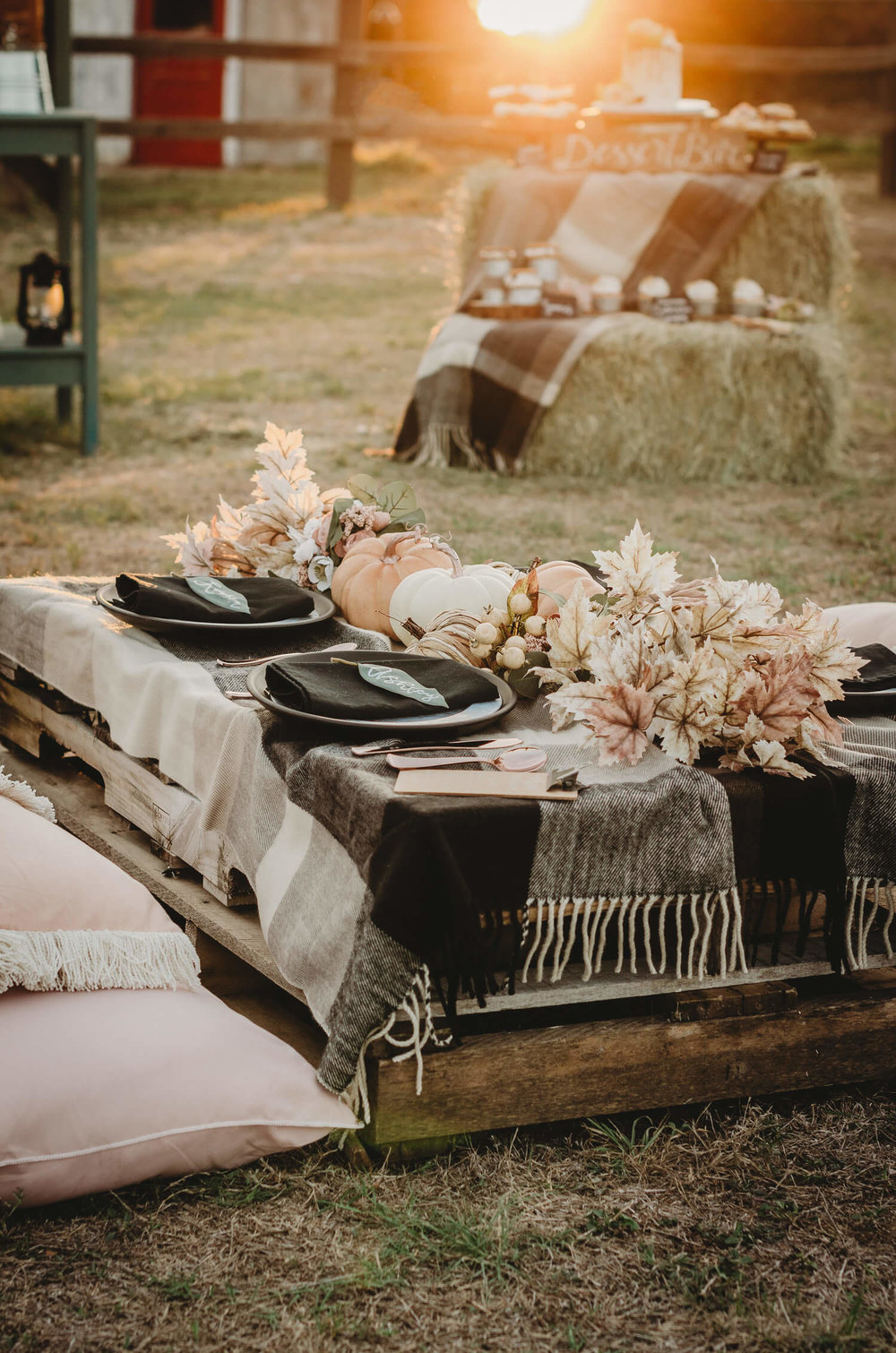 Create a low seating arrangement for a fall bridal shower on a farm with wooden palettes covered with a flannel throw and pillows surrounding. Click to see all the details of this fall bridal shower by party stylist Mint Event Design. #bridalshowers #bridalshowerideas #rusticwedding #rusticbridalshower #bridalshowerdecor #farmwedding #tablesetting