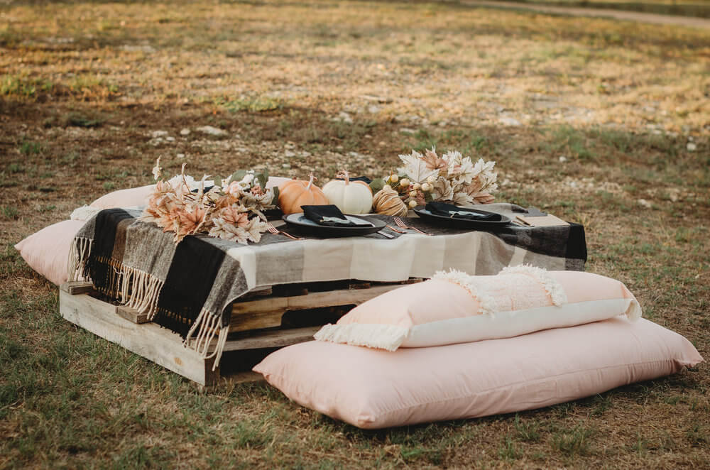 The cutest way to party with guests on farm bridal shower - create low seating with wooden palettes covered with a flannel throw and pillows surrounding for the seats. Click to see all the details of this fall bridal shower by party stylist Mint Event Design. #bridalshowers #bridalshowerideas #rusticwedding #rusticbridalshower #bridalshowerdecor #farmwedding #tablesetting