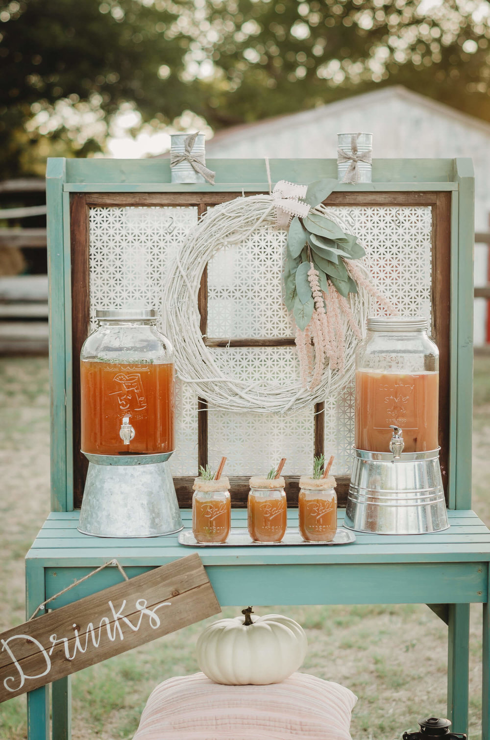 A gardeners tool table is the perfect choice for a rustic bridal shower drink station - especially when held on a farm. Click to see even more details of this fall bridal shower by party stylist Mint Event Design. #bridalshowers #bridalshowerideas #rusticwedding #rusticbridalshower #bridalshowerdecor #farmwedding #drinkstation #drinkbar