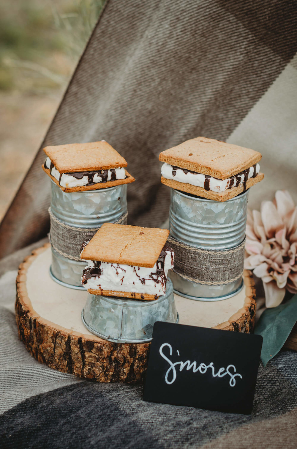 The best display for s'mores at a rustic bridal shower - a wooden charger with s'mores on inverted galvanized pails at different heights. Click to see many more bridal shower ideas from this Fall in Love party theme. Created by party stylist Mint Event Design. #bridalshowers #bridalshowerideas #rusticwedding #rusticbridalshower #bridalshowerdecor #farmwedding #partyideas #fallbridalshower #smores #bridaslshowerdessert #minidesserts