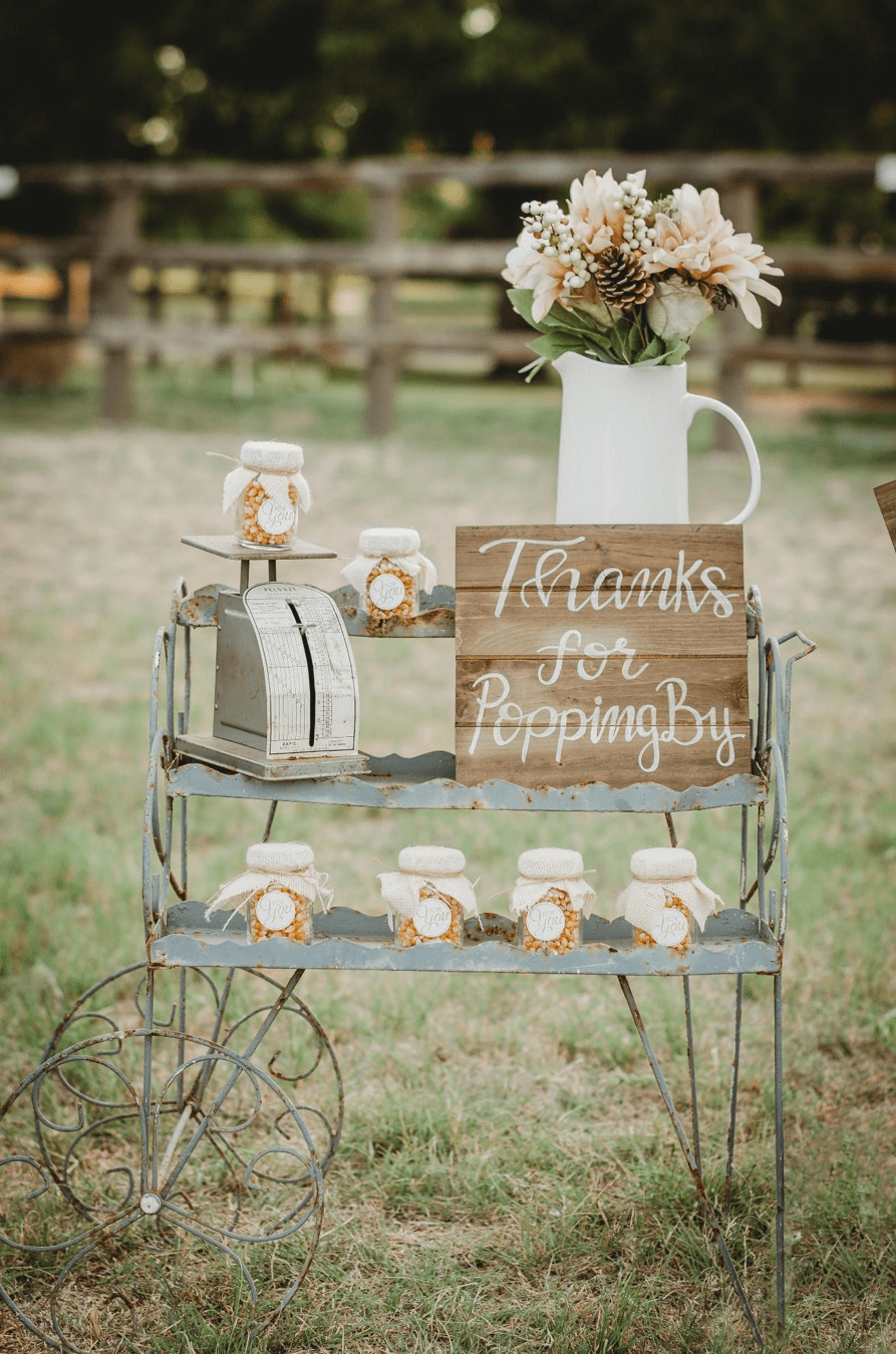 Dress up your party favor cart with florals and a vintage scale as a prop is perfect for a rustic bridal shower. Click to see even more rustic party ideas from this fall themed bridal shower. Created by party stylist Mint Event Design. #bridalshowers #bridalshowerideas #rusticwedding #rusticbridalshower #bridalshowerdecor #farmwedding #partyideas #fallbridalshower #woodensign #barcart