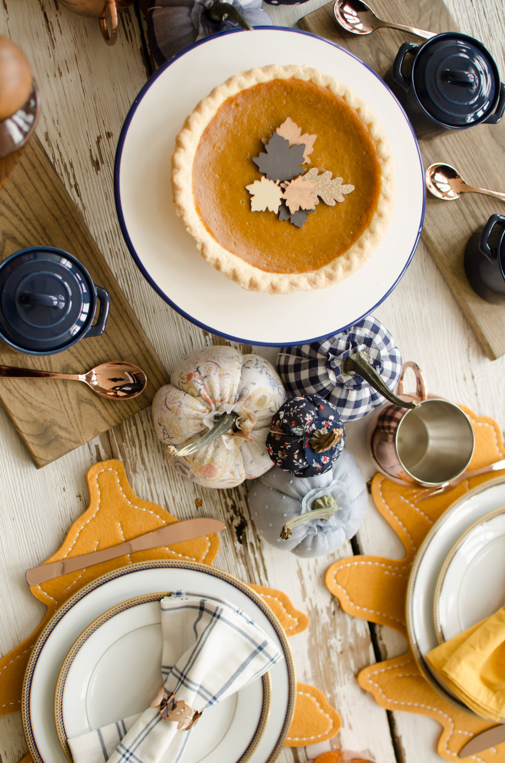 This Thanksgiving table is both shabby chic and so elegant with the copper and blue colors. Plus there's fabric pumpkins and fabric leaf shaped placemats. See more Thanksgiving Party Ideas from party planner, Mint Event Design in Austin, Texas on www.minteventdesign.com #thanksgiving #thanksgivingdecorations #tablescape #thanksgivingtable #pumpkins #tablesettings #fallparty