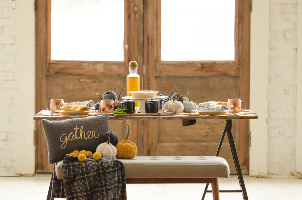 Thanksgiving table inspiration with a bench for seating and a cute Gather pillow. Lots of fabric pumpkins make the entire setting extra cozy. See more Thanksgiving Party Ideas from party planner, Mint Event Design in Austin, Texas on www.minteventdesign.com #thanksgiving #thanksgivingdecorations #tablescape #thanksgivingtable #pumpkins #tablesettings #fallparty