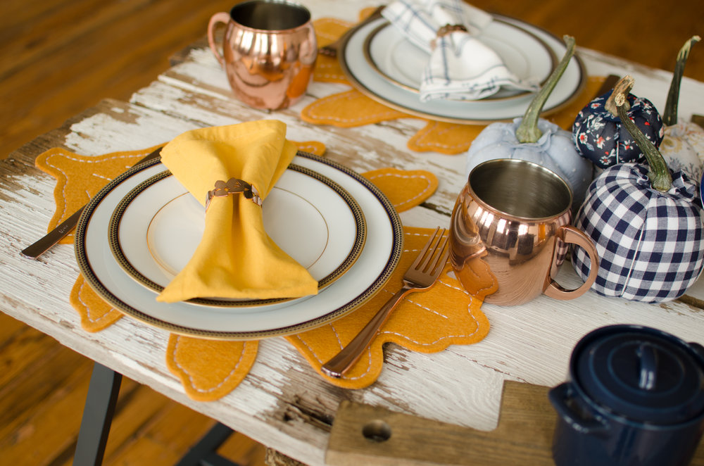 This chipped paint gives this table the perfect Fixer Upper look for Thanksgiving dinner. Click to see how to create a shabby chic Thanksgiving dinner table with party planner, Mint Event Design in Austin, Texas on www.minteventdesign.com #thanksgiving #thanksgivingdecorations #tablescape #thanksgivingtable #pumpkins #tablesettings #fallparty