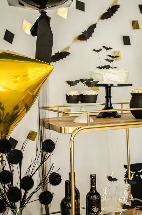 Loving the gold theme of this Halloween Party with a fancy black bat garland and black bat dessert toppers. Click to see more from this Bar Cart styling by party stylist Carolina of Mint Event Design. #partyideas #partyinspiration #halloween #barcart #barcartdecor #partystyling