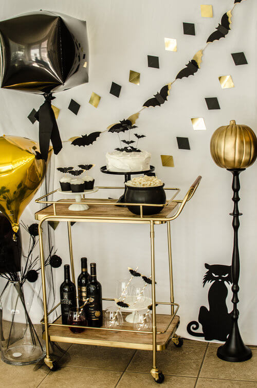 Simple and Elegant Halloween Bar Cart Idea in gold, black and white. There's even black wine bottles. Click to see more from this Bar Cart styling by party stylist Carolina of Mint Event Design. #partyideas #partyinspiration #halloween #barcart #barcartdecor #partystyling