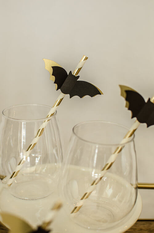 Elegant and Fun Halloween Party Ideas. Top your paper straws with black and gold bats at your Halloween party. Click to see more Halloween Party styling tips by party stylist Carolina of Mint Event Design. #partyideas #partyinspiration #halloween #partydrinks #partystyling