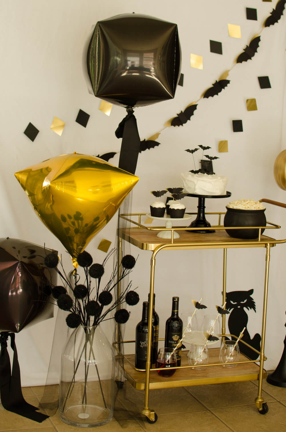Halloween Bar Cart Styling Tips: Include a bat garland with a diamond shaped garland and even gold and black balloons in different shapes to fill in the space. Instead of flowers, use spooky black twigs with black pom poms in an oversize glass vase. Click to see more from this Bar Cart styled by party stylist Carolina of Mint Event Design. #partyideas #partyinspiration #halloween #barcart #barcartdecor #partystyling