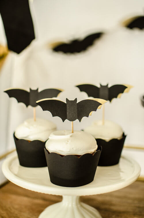 Cute Batty Cupcakes for a Halloween Bash. Paper Bat cupcake toppers are fun and classy for this Halloween Bar cart styling by party stylist Carolina of Mint Event Design. #partyideas #partyinspiration #halloween #halloweencupcakes #cupcaketoppers