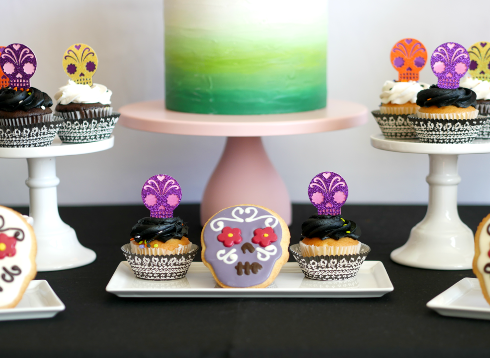 Colorful Day of the Dead themed dessert table with sugar skull cookies and sugar skull cupcake toppers. Click for more Day of the Dead party ideas for a dessert table on the Mint Event Design party blog from Austin, Texas based party stylist www.minteventdesign.com #dayofthedead #diadelosmuertos #sugarskulls #mexicanparty #halloweenparty #partyideas