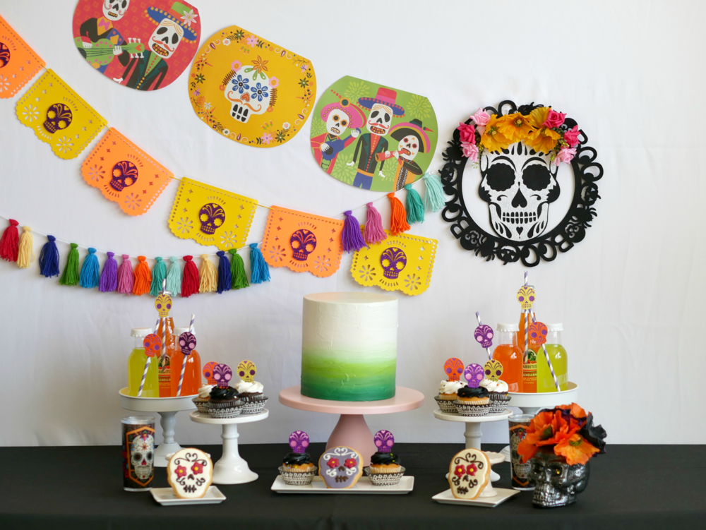 Sugar skull decorations and papel picado banners create the perfect dessert table backdrop for this Day of the Dead Halloween Party. Find more Dia de Muertos party inspiration on the Mint Event Design party blog www.minteventdesign.com #dayofthedead #diadelosmuertos #sugarskulls #mexicanparty #halloweenparty #partyideas #papelpicado