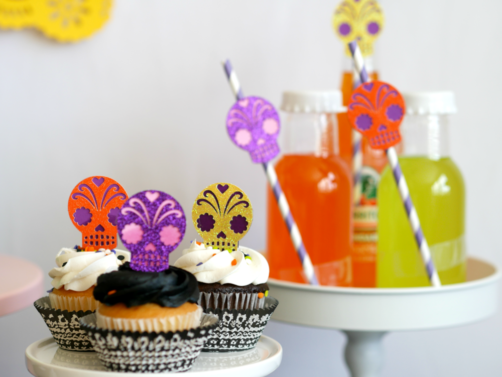 Skull decorations and cupcake toppers at this Day of the Dead party add fun and can even be attached to party straws for extra fun color. Find more Dia de Muertos party inspiration on the Mint Event Design party blog www.minteventdesign.com #dayofthedead #diadelosmuertos #sugarskulls #mexicanparty #halloweenparty