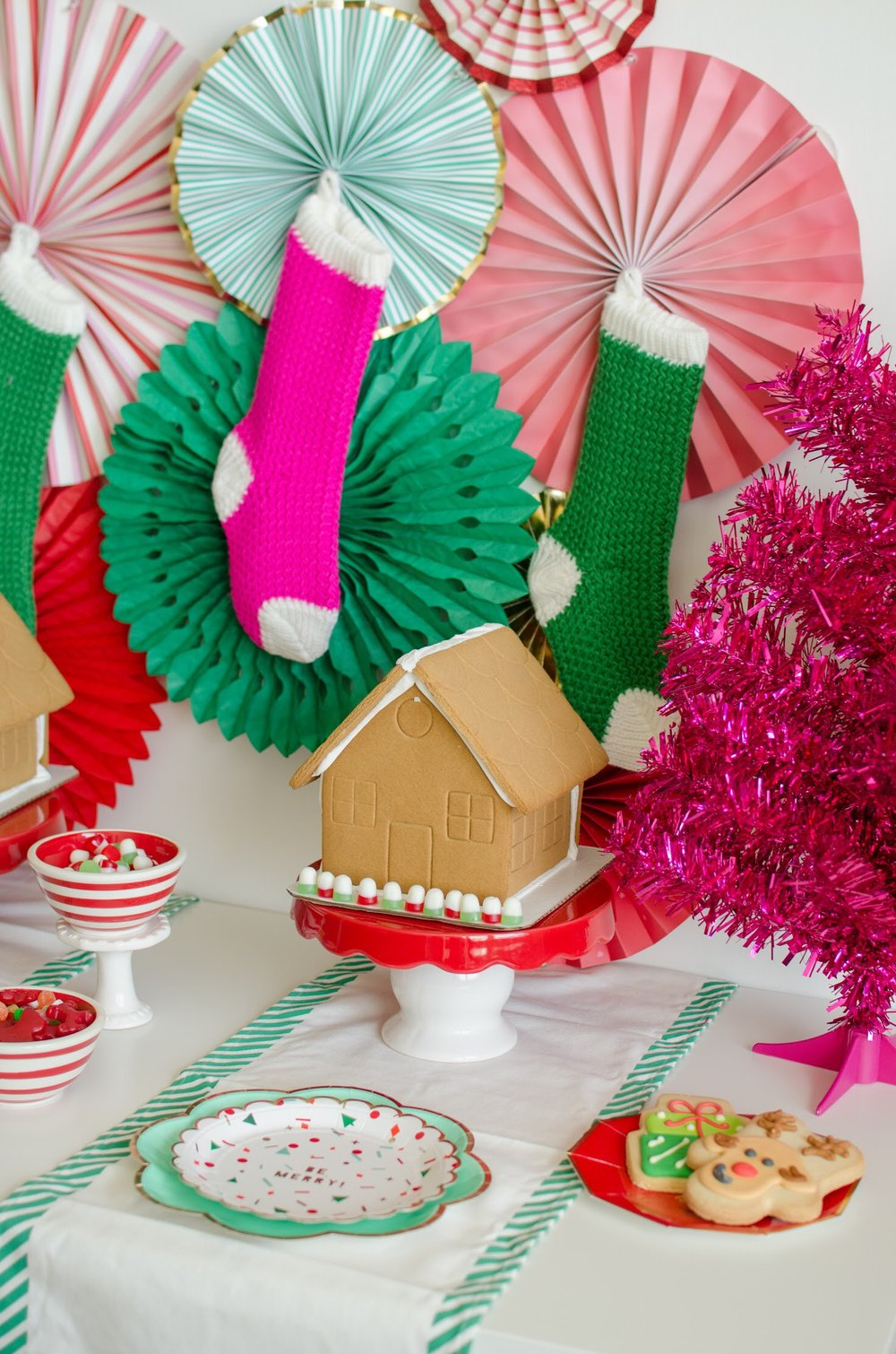 Create the perfect Gingerbread House Party backdrop with knit stockings and paper fans in bright holiday colors. See the full decorating details and party set up design on Mint Event Design www.minteventdesign.com #gingerbreadhouse #holidayparty #holidays #partyideas #christmasparty #holidaypartyideas #kidsparty
