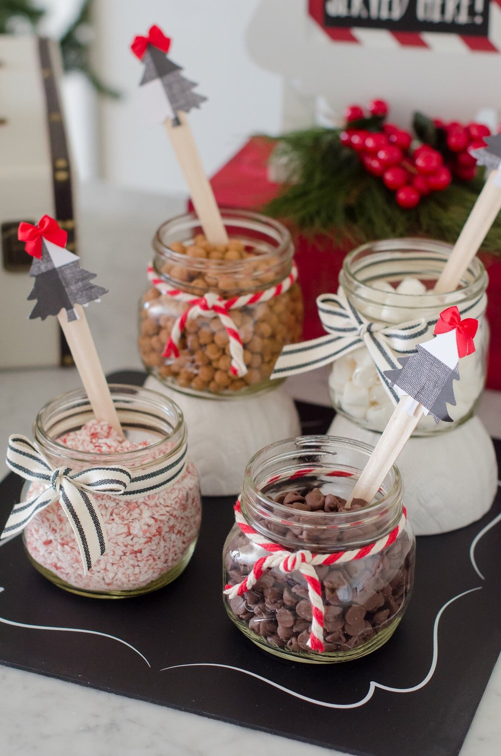 Don't forget the toppings to create a beautiful hot cocoa station. Serve them in decorated mason jars with wooden spoons decorated with paper trees on top. See more holiday party inspiration from Austin based party stylist Mint Event Design at www.minteventdesign.com #holidayparty #holidays #partyideas #christmasparty #holidaypartyideas #hotcocoabar #hotcocoa