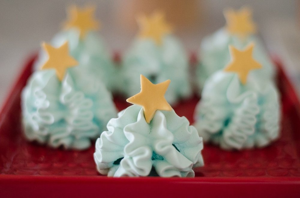 These Christmas tree meringues topped with stars are just the cutest - perfect for your Christmas party. See more holiday party inspiration from Austin based party stylist Mint Event Design at www.minteventdesign.com #desserttable #christmasdesserts #holidayparty #holidays #partyideas #christmasparty #holidaypartyideas #meringues