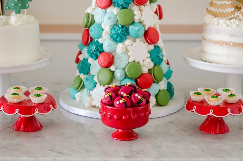Macaron tree and assorted Christmas party desserts served in pretty red bowls and red cake stands. See more holiday party inspiration from Austin based party stylist Mint Event Design at www.minteventdesign.com #desserttable #christmasdesserts #holidayparty #holidays #partyideas #christmasparty #holidaypartyideas