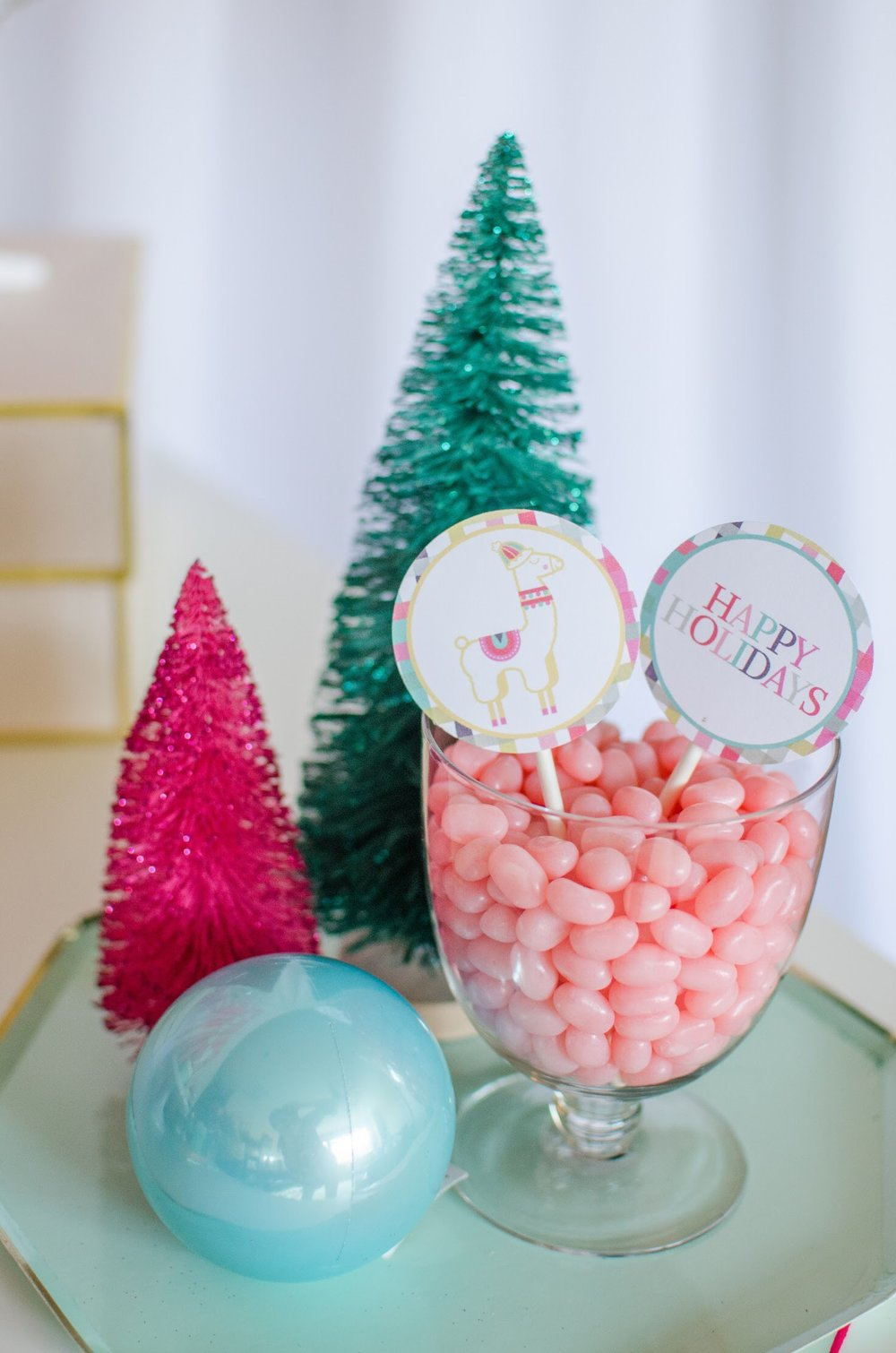 Colorful candy and bottle brush trees dresses up the sweets table at this fa la la la llama holiday party from Mint Event Design. See more from this llama Christmas party at www.minteventdesign.com and download your free printables #holidayparty #partyideas #christmasparty #holidaypartyideas #llamaparty #llamalove