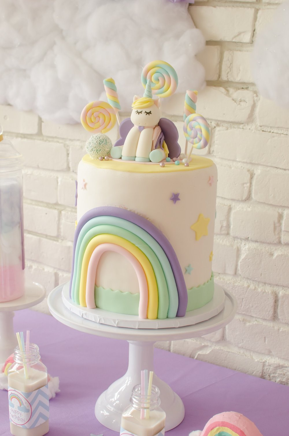 The cutest unicorn topper on a pastel rainbow unicorn cake. See more from this unicorn birthday party at Mint Event Design www.minteventdesign.com #unicornparty #unicorncake #birthdayparty #birthdaypartyideas #birthdaydesserts #birthdaycake